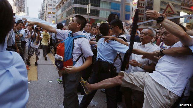 Pro-democracy protester argues with an anti-Occupy Central protester while being kicked by another anti-Occupy Central protester at Hong Kong's shopping Mongkok district on 3 October 2014