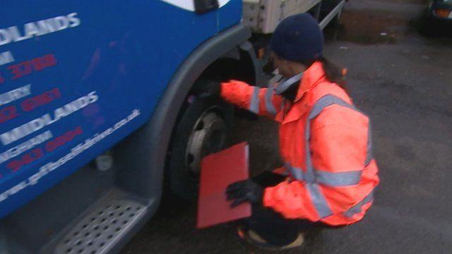 Man checking lorry tyre