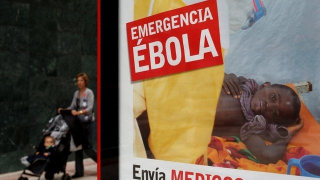 "A woman walks an infant on a pushchair next to a bus stop banner reading ""Emergency Ebola. Send doctors"" in Spanish"