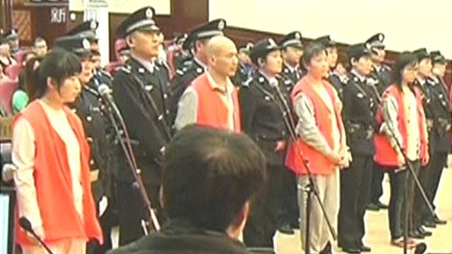 Defendants stand during their trial for the murder of a woman at a McDonald's restaurant, in Yantai City