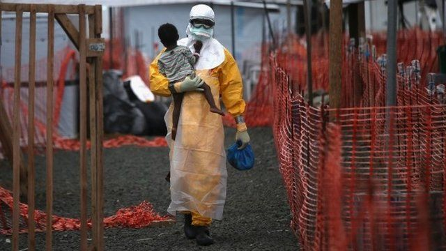 A Doctors Without Borders (MSF) health worker in protective clothing carries a child suspected of having Ebola in the MSF treatment centre in Paynesville, Liberia, 5 October 2014