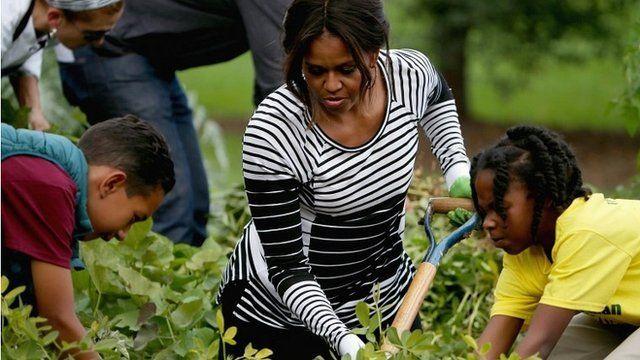 Michelle Obama and children harvesting vegetables