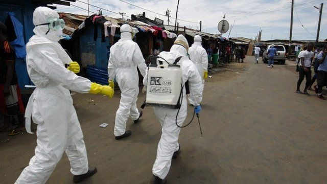 A Liberian Red Cross burial team on the move to pick up a suspected Ebola victim in the impoverished area of West Point, Monrovia, Liberia