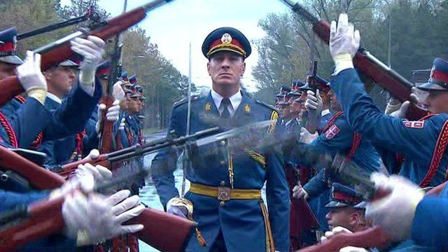 A Serbian soldier performing a ceremonial march through the rifles of two ranks of soldiers