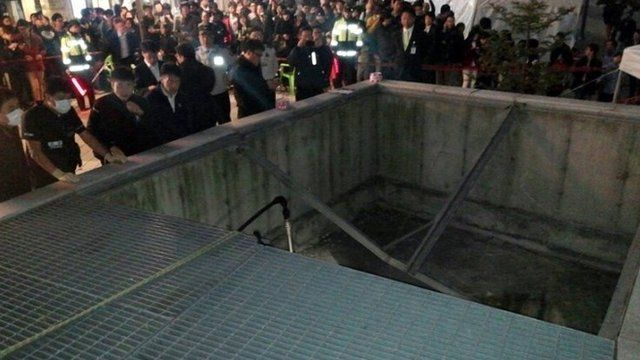 People gather around a collapsed ventilation grate at an outdoor theatre in Seongnam, south of Seoul, South Korea, Friday, Oct. 17, 2014.