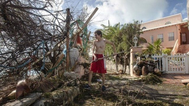 Man cleaning up after Hurricane Gonzalo
