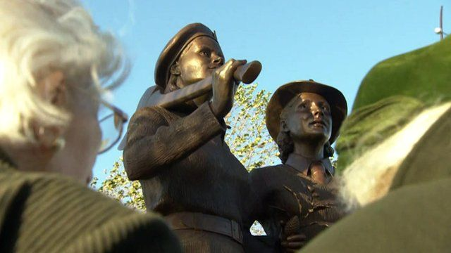 Close up of Land Girls monument with two veterans standing in front of it