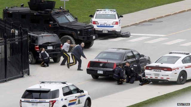 Police officers take cover near Parliament Hill