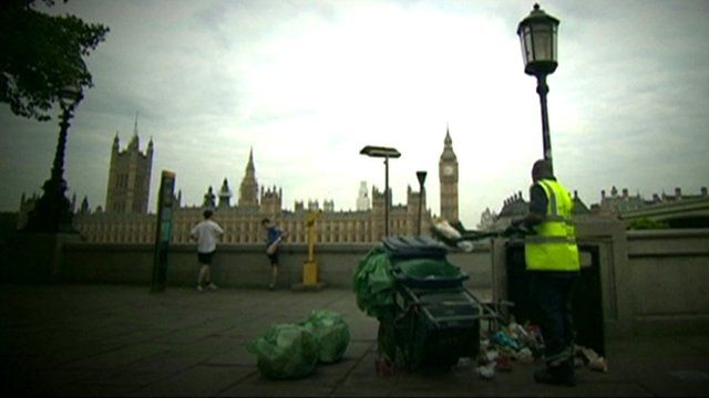 Man clearing rubbish into cart with Westminster in the background