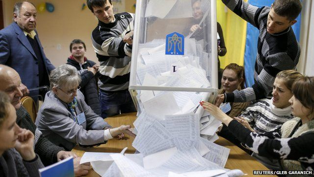 People tipping ballot papers out of a box ready for counting following Ukraine's parliamentary election on 26 October 2014