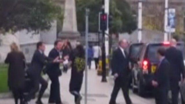 Still of a man running into David Cameron