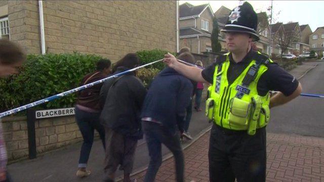 People cross police tape on Blackberry Road in Bradford