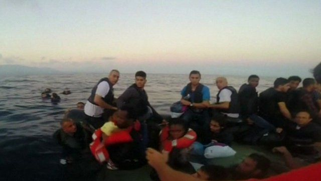 Migrants on a raft in the sea, having just been saved, some in lifejackets
