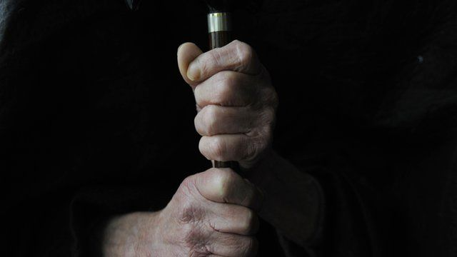 Elderly person holding cane