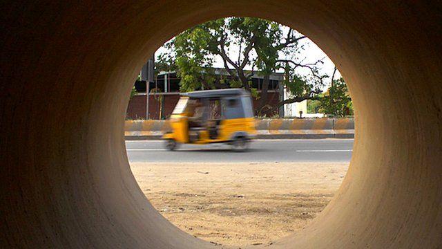 Rickshaw through a concrete pipe