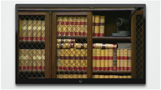 Television screen shows camera nestled amongst books on a shelf within the Royal Courts of Justice