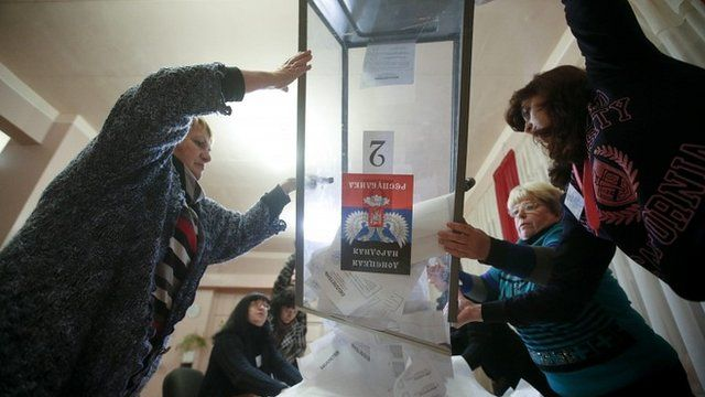local electoral commission empty a ballot box at a polling station after voting day in Donetsk