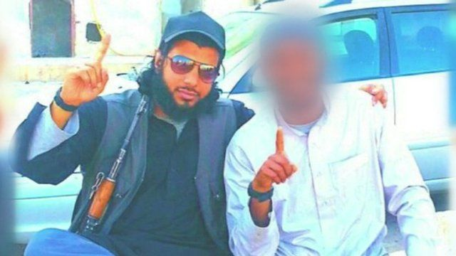 Kabir Ahmed with an assault rifle sitting next to another man whose identity has been obscured