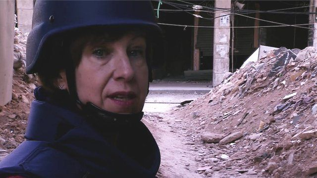 BBC reporter Lyse Doucet in front of an alleyway of rubble in the Syrian city of Aleppo
