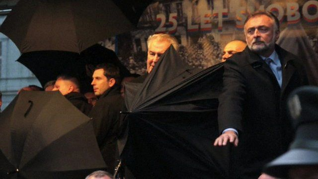 Milos Zeman surrounded by bodyguards with umbrellas