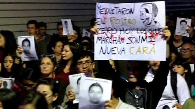 Protesters holding images of missing Mexico students