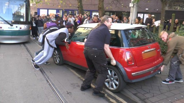 Bystanders lifting the car