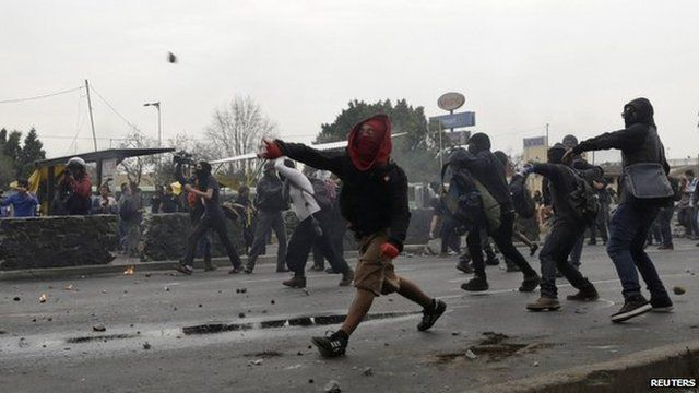 Masked demonstrators throw rocks towards riot police during a protest over the 43 missing Ayotzinapa students, near the Benito Juarez International airport in Mexico City on 20 November 2014.
