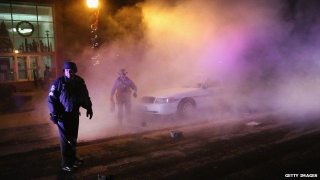 Police stand guard in front of a smouldering squad car after it was set on fire by demonstrators in Ferguson, Missouri