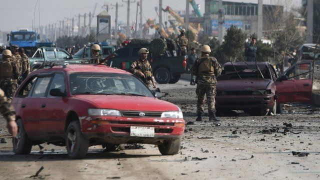 Afghan intelligence personnel inspect the site of a suicide attack on a British embassy vehicle along the Kabul-Jalalabad road in Kabul