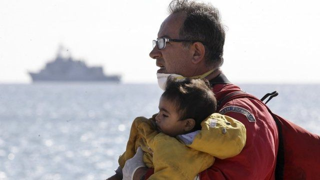 A rescuer carries a child evacuated from a cargo ship
