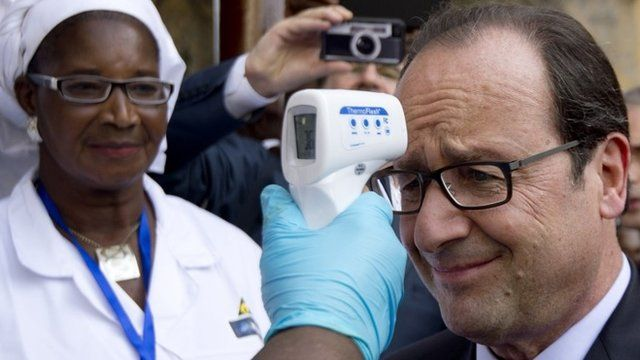 President Hollande has his temperature measured at a hospital in Conakry