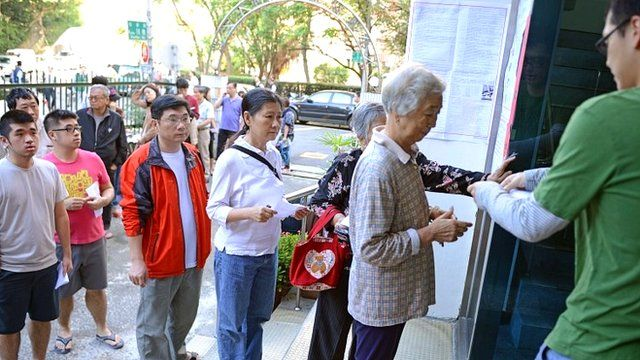 Residents line up for their ID checking before vote at a polling station in Taipei