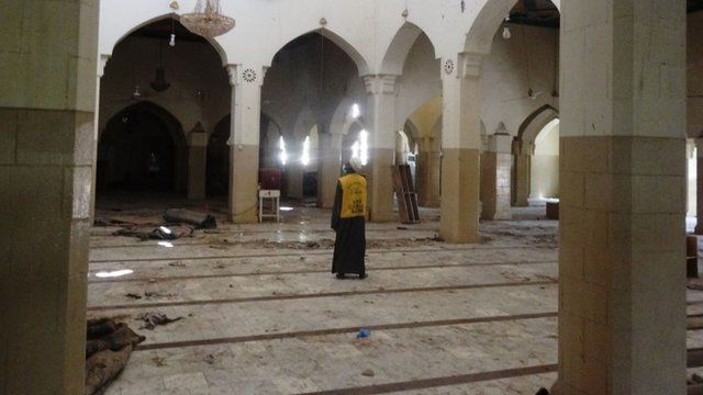 """A mosque official surveys damage in the central mosque in northern Nigeria""""s largest city of Kano on November 29, 2014"""