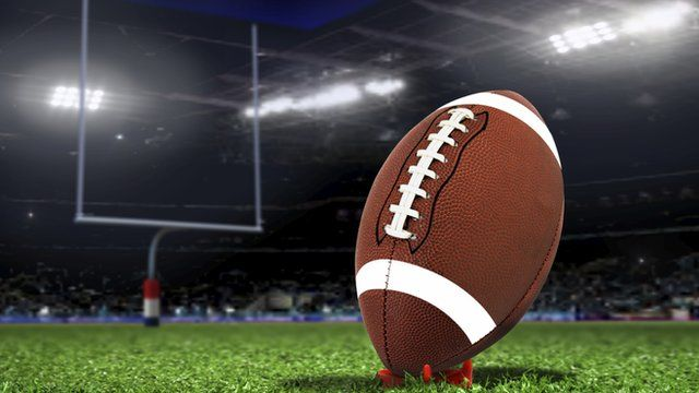 Stock image showing a football in front of a goal post