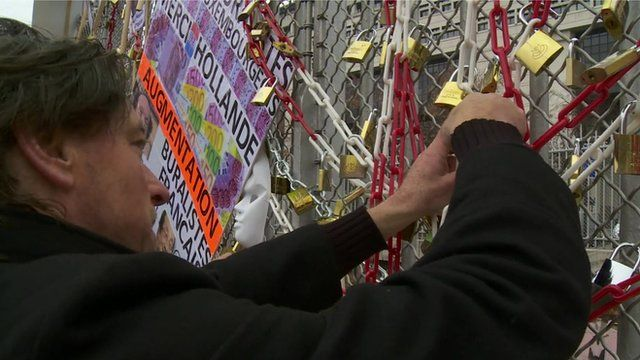 French business protester attaching padlocks and chains to fencing outside France's Finance Ministry in Paris