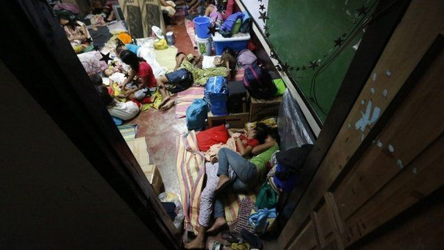 Filipino residents rest inside a school classroom turned into a temporary evacuation center in Tacloban city