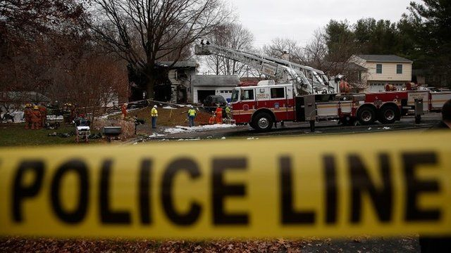 Utility workers and emergency personnel work near the site where a small plane crashed into a residential neighbourhood