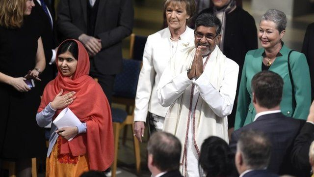 Satyarthi (R) and Malala Yousafzai (L) salute guests upon arrival for the Nobel Peace Prize awarding cere