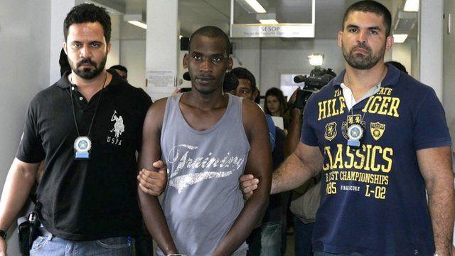 Sailson Jose das Gracas, 26, is escorted by policemen