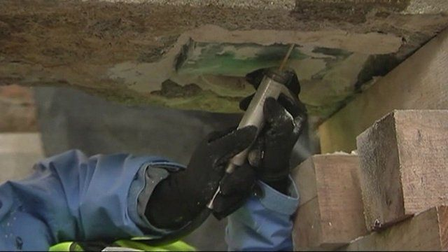 Man working to remove time capsule from concrete slab