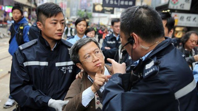 member of the public argues with police when asked to leave the pro-democracy protest site in the Causeway Bay district of Hong Kong on December 15, 2014
