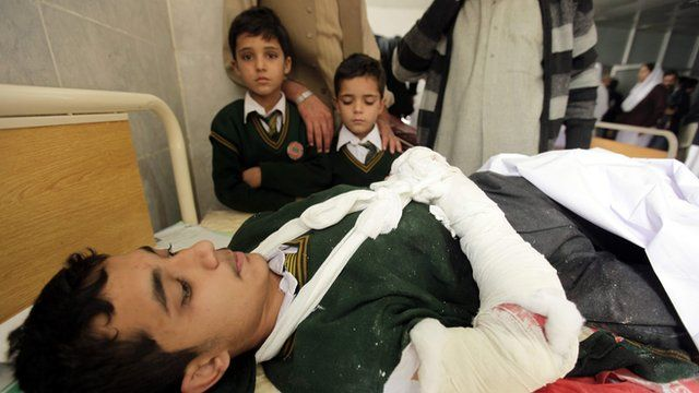An injured boy with two other children by his bedside