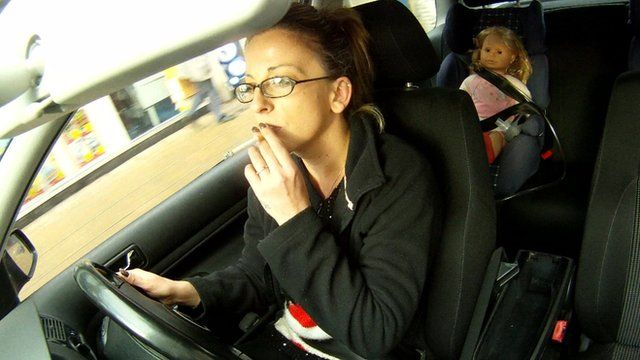 Woman smokes with child dolls in the back seats