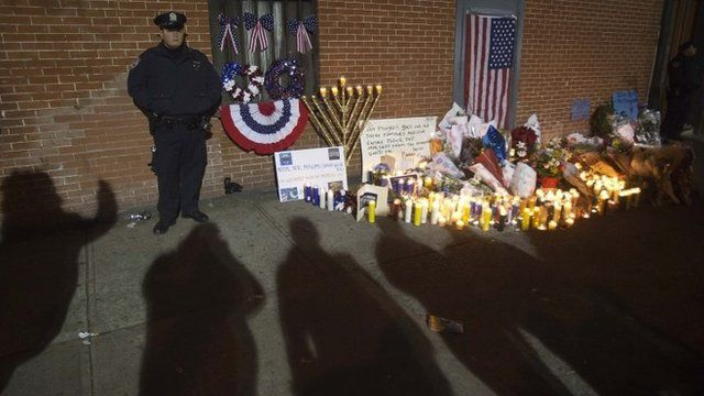 Candlelit vigil guarded by police for slain NYPD officers