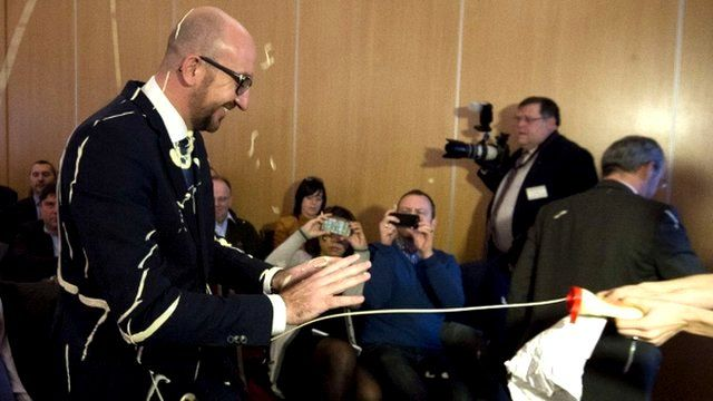 Female protestor squirts Belgian Prime Minister Charles Michel with mayonnaise