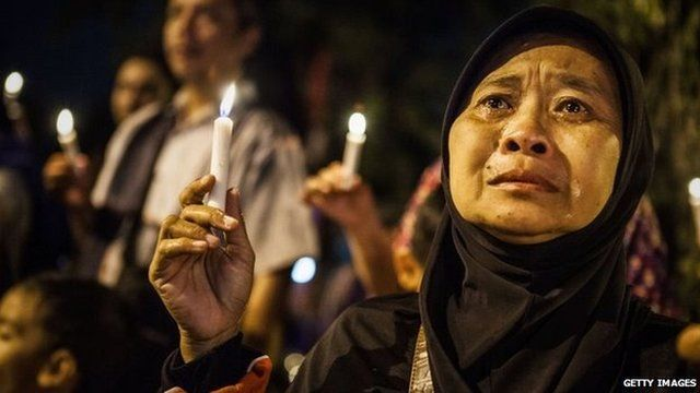 A woman cries as she prays for the victims of the AirAsia flight QZ8501 crash at the Indonesian Air Force Military Base Operation Airport in Surabaya, Indonesia, 31 December 2014