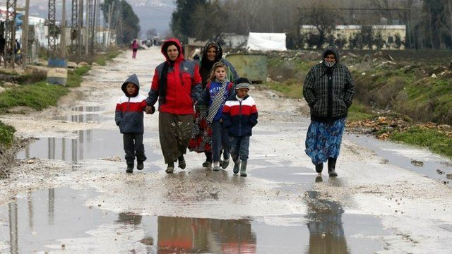 Syrian refugees walk along a makeshift settlement in Bar Elias in the Bekaa valley January 5, 2015