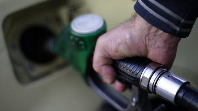 A man fills up his car at a petrol station