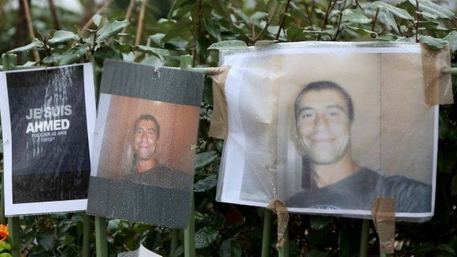 """Flowers and banners are placed on the ground where the french policeman Ahmed Merabet has been killed by the two gunmen who attacked the french satirical """"Charlie Hebdo"""""""