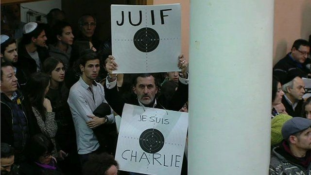 Man in synagogue holding placards